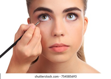 Girls hand Drawing the right eye with a brush close-up on a white isolated background
