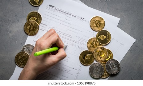 The girl's hand fills the tax form for paying taxes from the mining and trading of crypto-currencies.