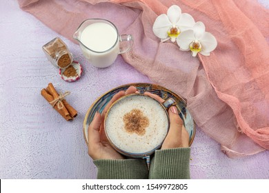 Girl's hand hold Traditional Turkish Drink Salep. Turkish salep (milky traditional hot drink).