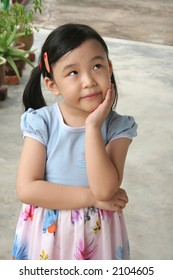 Girl's hand holding chin with wondering expression in a daze