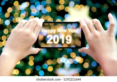Girl's hand holding mobile phone take a photo of christmas tree with wording Happy New Year 2019. Young woman using smartphone outdoor capture picture of bokeh blur Christmas lighting lamp decoration.