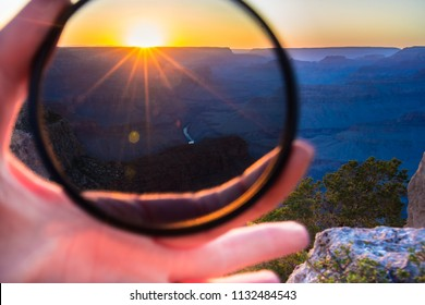 Girls hand holding warming, neutral density or polarizing high quality glass filter to put on her camera lens to make Grand Canyon with Colorado river sunset landscape photo background.