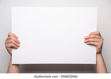 Girls hand holding a white board
