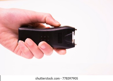 The girl's hand holds an Electroshocker. Self-defense. White background.