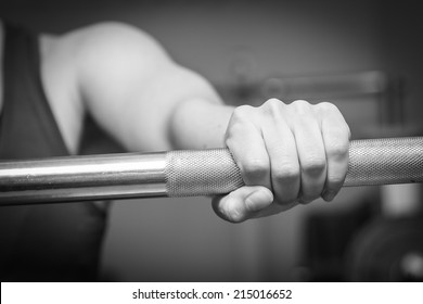 Girl's hand on the barbell. Beautiful girl goes in for sports in the gym. Girl holding a barbell. Gym, strength, fitness - Healthy lifestyle concept. Article about women's fitness.