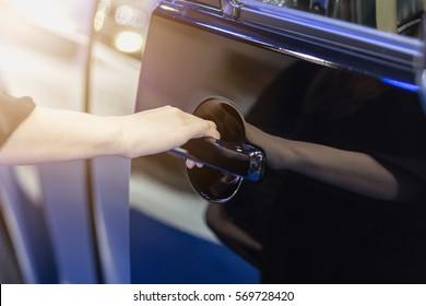 Girl's hand pulling a car's door handle