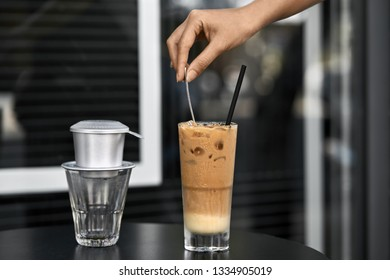 Girl's hand puts a spoon in the ice coffee drink with ice cubes in a wet cold glass with a black straw on the dark table in the outdoor cafe on the blurred background. Empty glass near them. Closeup.
