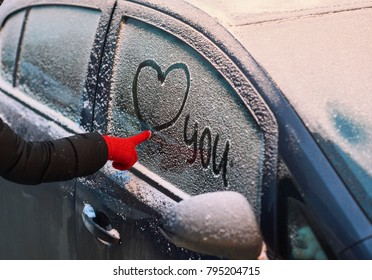 """The girl's hand in a red glove draws the heart and the word """"you"""" on the snow-covered glass of the car"""