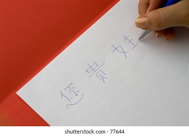 Girl's hand, writing Chinese characters, on white paper on top of red folder.
