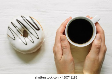 Girl's hands with cup of coffee and glazed white chocolate donut behind. Light wooden background