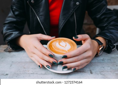 girl's hands with freckles around a cup of coffee. hot coffee with foam on which there is a picture