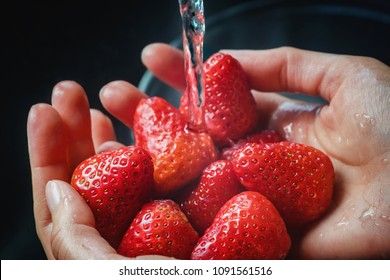 Girls hands with fresh strawberries under the tap of the water. Close up.