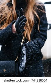 Girls Hands in gloves shaking snow. Close-up