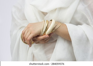 Girl's hands with golden bracelets on a white cloth