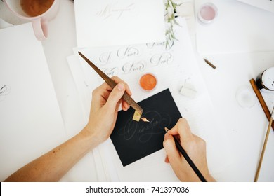 The girl's hands hold a brush and a pen for writing with a typographical handwriting. Caligraphy and lettering.