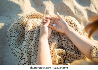 girl's hands hold a small shell. Beautiful sunset on the beach. Concept - sad mood
