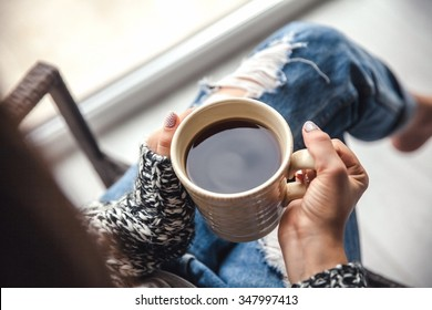 Girl's hands holding a cup of coffee, ripped jeans. Fashion manicur