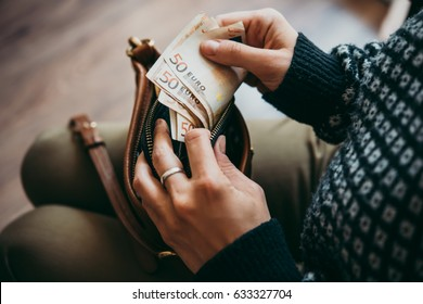 Girl's hands holding euro bills, small money pouch and leather bag
