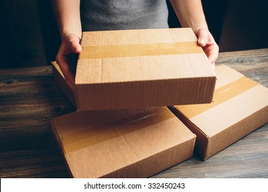 Girl's hands holding the package on the table