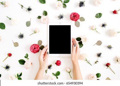 Girl's hands holding tablet on floral frame with red and beige rose flower buds on white background. Top view, flat lay decorated concept.