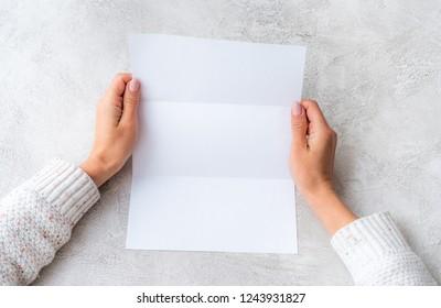 Girl's hands holding white molded sheet of paper