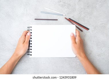Girl's hands holding white notebook on gray background