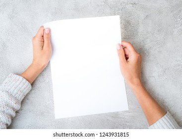 Girl's hands holding white sheet of paper vertically