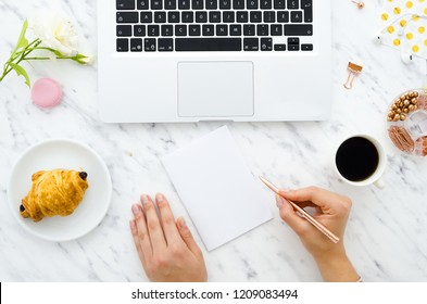 Girl's hands holds golden pen. Workspace with laptop, earphones, notebook, coffee, office supplies on marble background. Flat lay, top view office table desk. Freelancer working place mockup template