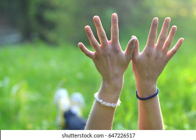 girl's hands lying in the grass