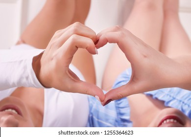 Girls hands making heart sign. Homosexual couple on bed at home. Conceptual photo about homosexuality, lesbians and LGBT. 17 May - International Day against Homophobia.