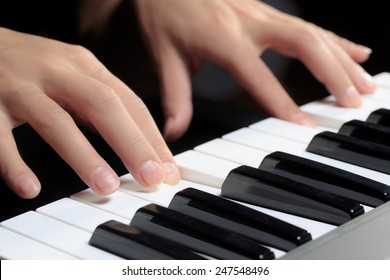 Girl's hands on the keyboard of the piano