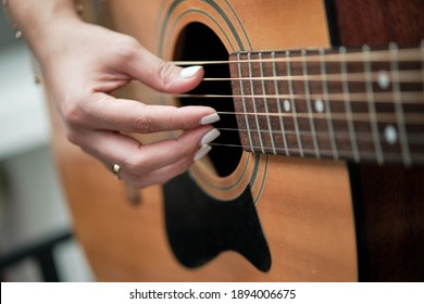 girl's hands playing an acoustic guitar