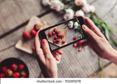 女孩的手采取早餐与草莓智能手机的照片。 健康的早餐,干净的饮食,素食主义者的食物概念。 顶视图