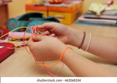 Girl's hands weaving a plastic bracelet.