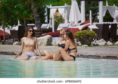 Girls hanging out at a summer club pool. Sunbathing while having a chat.