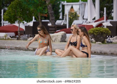 Girls hanging out at a summer club pool. Sunbathing and having fun