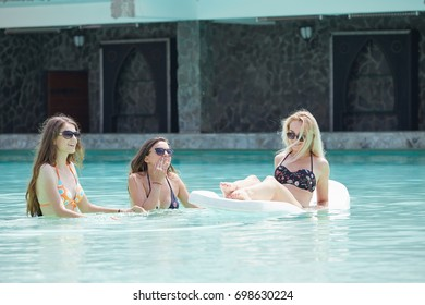 Girls hanging out at a summer club pool. Having fun in the water.