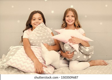 Girls happy best friends or siblings in cute stylish pajamas with pillows sleepover party. Sisters play pillows bedroom party. Pillow fight pajama party. Evening time for fun. Sleepover party ideas.