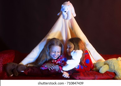 Girls with happy faces lie under blanket tent on dark background. Childhood and happiness concept. Kids in pajamas covered with blanket play with white teddy bear. Children have pajama party