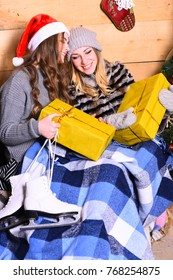 Girls with happy faces near Christmas tree on wooden wall background. Winter holidays and concept. Ladies in Santa hats hold yellow presents for xmas. Women with gift boxes, skates and blue blanket