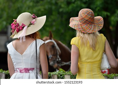girls with hats look at the horse racing, derby