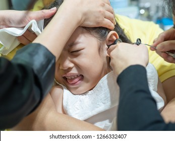 Girls have Cerumen impaction or Earwax blockage symptoms. Treat by drops the Cerumenolytic agents into the ear for soften and suction out by doctor.