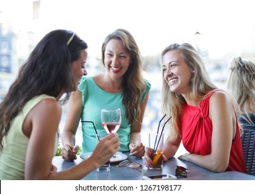Girls having chat and enjoying each other's company over a drink in a bar.