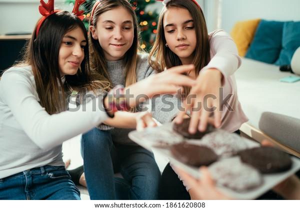 Girls having fun at home eating Christmas cookies