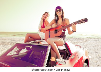 girls having fun playing guitar on th beach with a convertible car