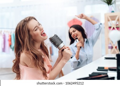 Girls are having fun in the showroom. Girls sing and hold a comb in their hands. They are sitting in a bright room opposite the mirror.