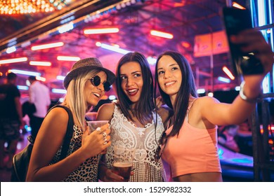 Girls having fun and taking selfie in the amusement park
