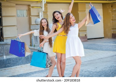 Girls having fun together. Girls holding shopping bags and walk around the shops. Beautiful girl dressed in dresses