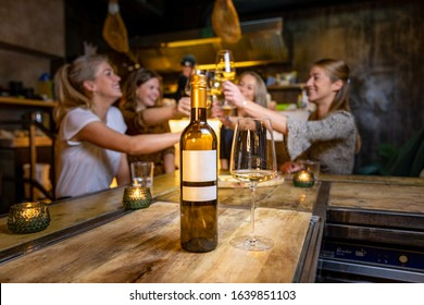 Girls having fun in a wine bar with a bottle of wine in the foreground and girls clinking their glasses in the background