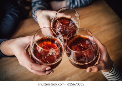 Girls having good time,cheering and drinking alcoholic cocktails, enjoying friendship together in coffee shop, close up view on hands